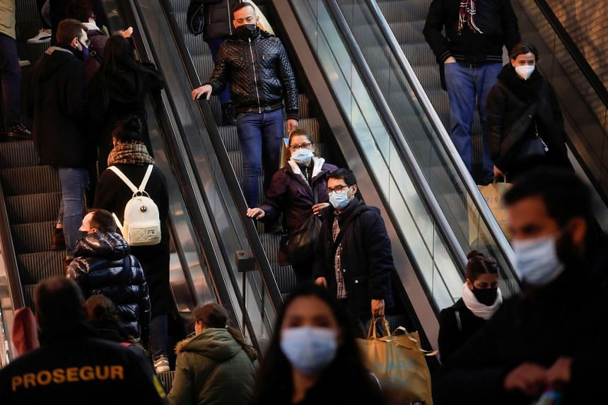 Shoppers wearing masks to protect against coronavirus ride escalators in Madrid, Jan 22, 2021.