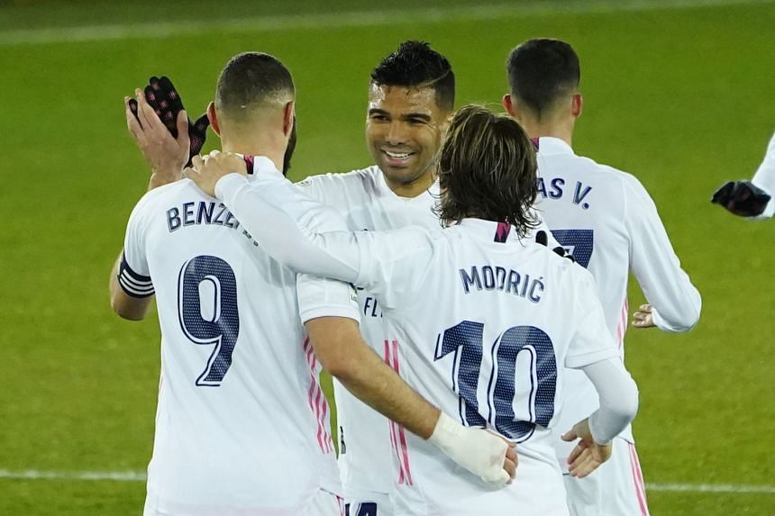 Benzema celebrates scoring Real's fourth goal with Casemiro and Luka Modric.