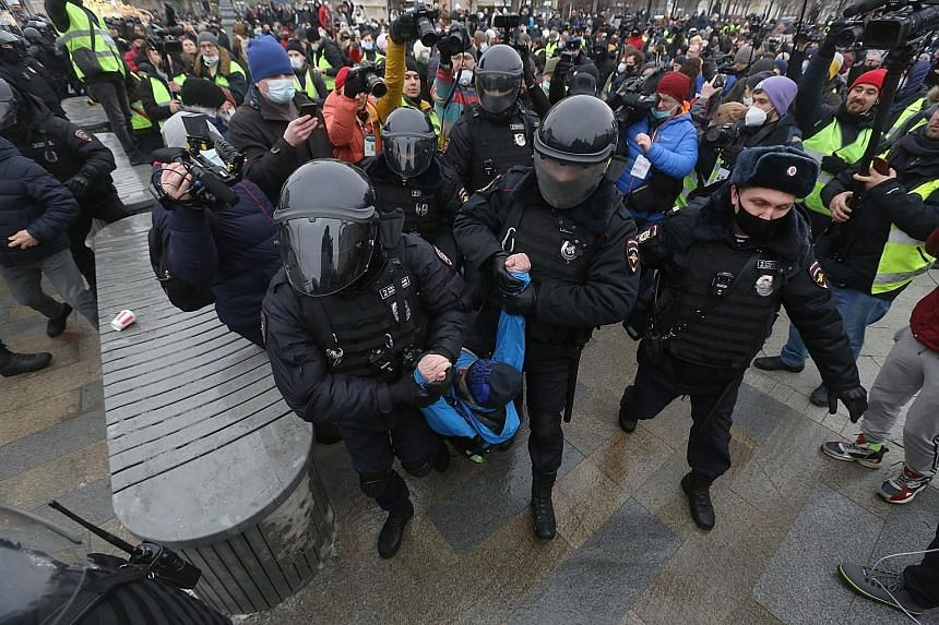 "Police in full riot gear beating protesters with batons yesterday in Vladivostok, where demonstrators had congregated in the city centre, chanting ""Putin is a thief"" and ""Freedom to Navalny"". Above: People in Omsk, Siberia, heeding Kremlin critic Ale"