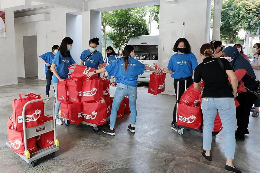 Volunteers yesterday preparing to send out festive packs containing food items such as soya milk powder, instant noodles, coffee, sunflower oil and oatmeal to residents living in rental units in the North West District. PHOTO: LIANHE ZAOBAO