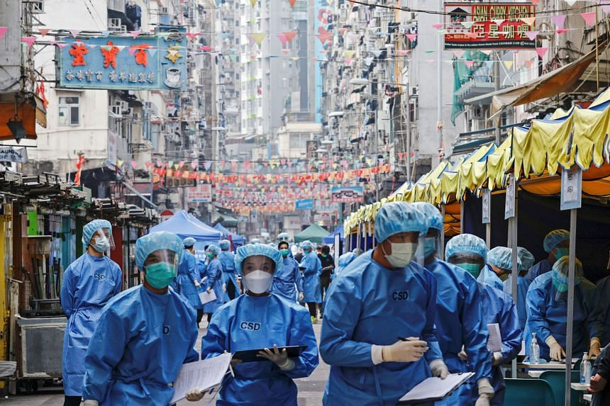 Health workers in protective gear inside a locked-down portion of the Jordan residential area in Hong Kong yesterday. More than 3,000 government staff were deployed to set up 51 testing stations and to go door to door to get people to go for the Covi