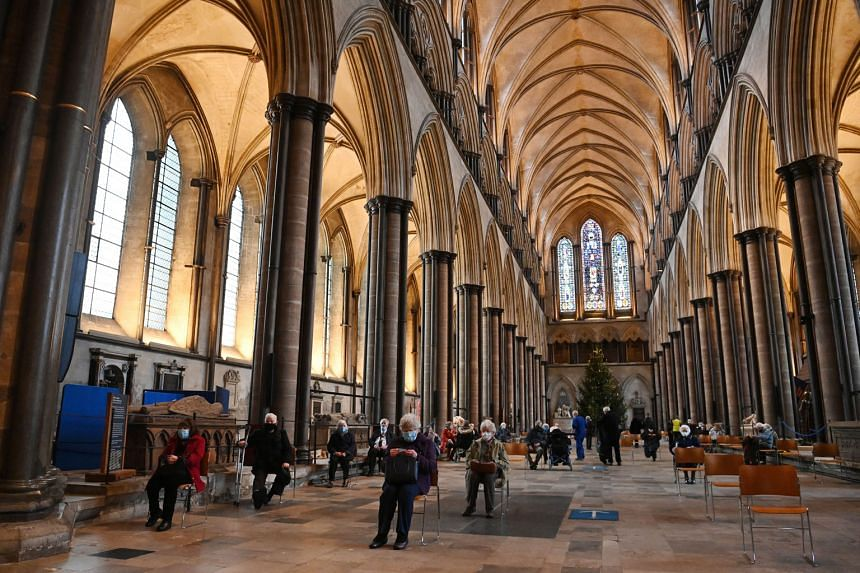 People resting in a waiting area after getting the Pfizer-BioNTech vaccine at Salisbury Cathedral in Britain. Prime Minister Boris Johnson said the country may need to roll out additional measures to safeguard its borders from new Covid-19 variants.