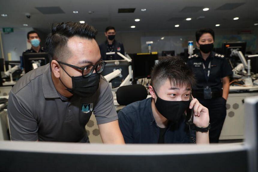 ST reporter David Sun answering a simulated 999 call as civilian officer Mohamad Suhaimi Bin Ami (left) looks on.