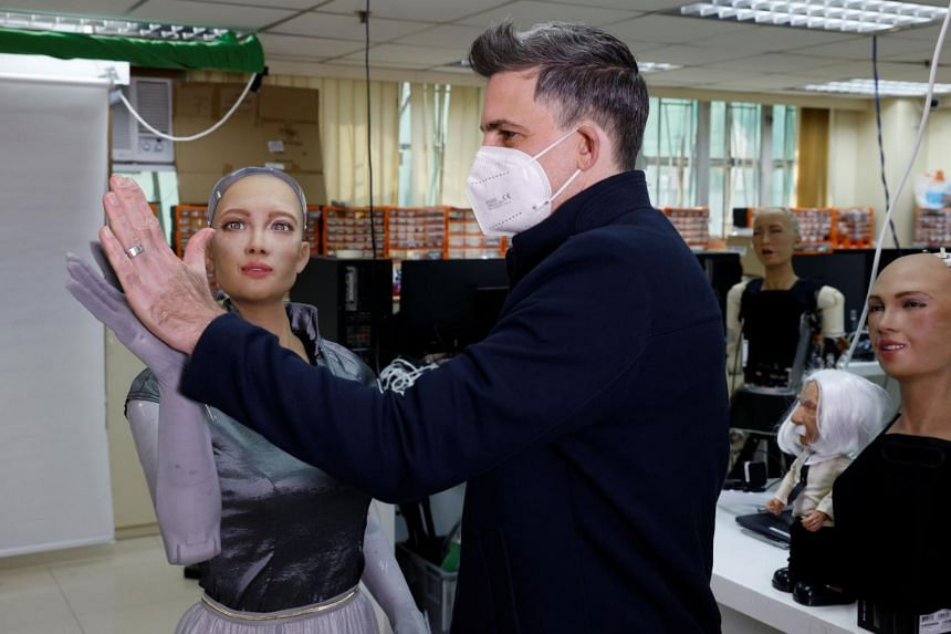 David Hanson gives a high-five to humanoid robot Sophia at the company's lab in Hong Kong, on Jan 12, 2021.