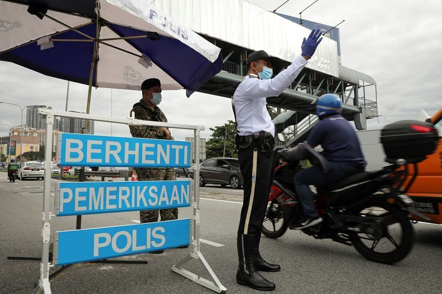 A police officer and a soldier stand guard at a roadblock to enforce lockdown, amid the Covid-19 outbreak, in Kuala Lumpur, on Jan 13, 2021.