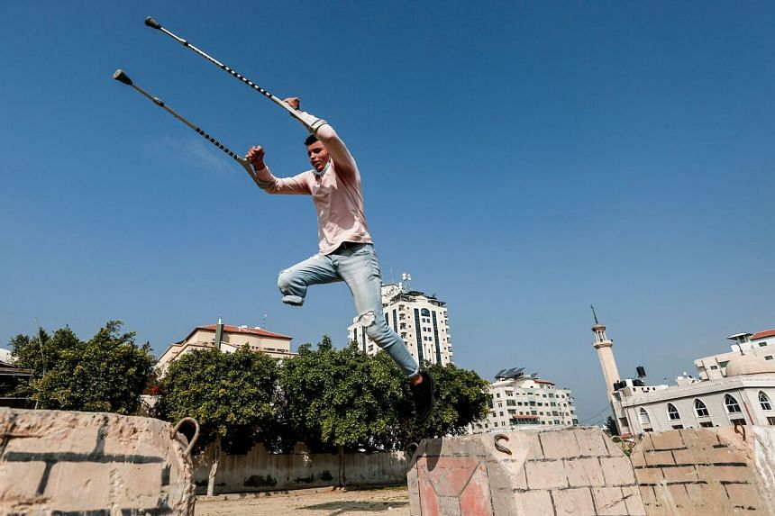 Mohamed Aliwa shows off his parkour skills despite his disability and while on crutches in Gaza City, on Jan 4, 2021.