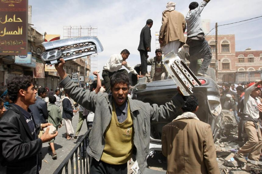 Anti-government protesters destroy a vehicle during a protest outside Sanaa University, in Yemen, on Feb 22, 2011.
