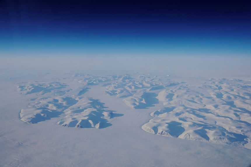 Glacial ice is seen from the window during a Nasa flight above the east coast of Greenland in a photo taken on March 13, 2018.