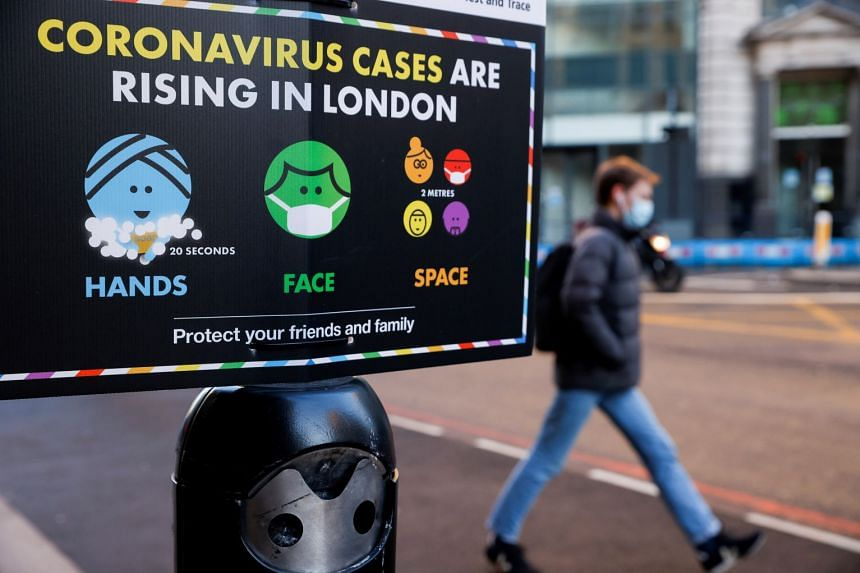 A man walks past a government sign with instructions about Covid-19 in London, Jan 25, 2021.