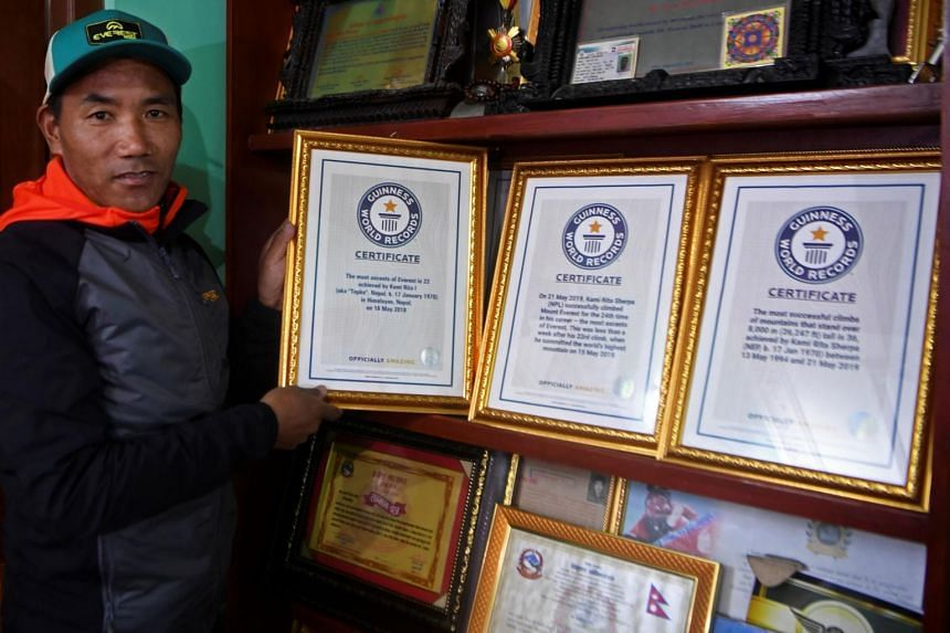 Nepal's mountaineer Kami Rita Sherpa, who has climbed Everest a record 24 times, poses with his certificates.