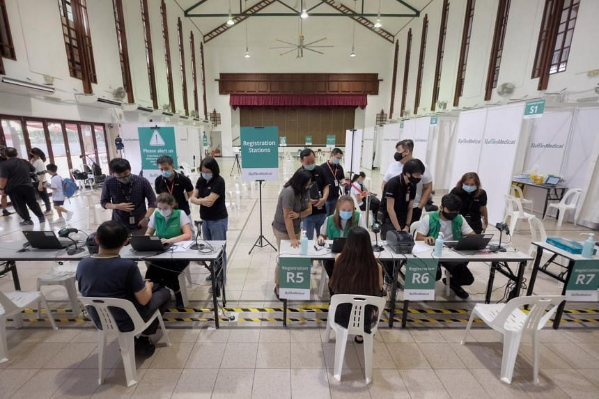 Volunteers wait to get the Covid-19 vaccine as they participate in a trial run at the vaccination centre in Tanjong Pagar Community Club on Jan 26, 2021.