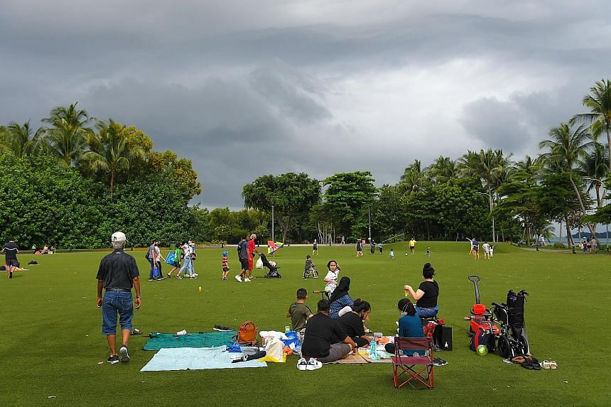 Families having a day out at Palawan Green in Sentosa last July, during phase two of Singapore's reopening after the circuit breaker period. Education Minister Lawrence Wong says he hopes that Singapore will emerge from the Covid-19 battle as a faire