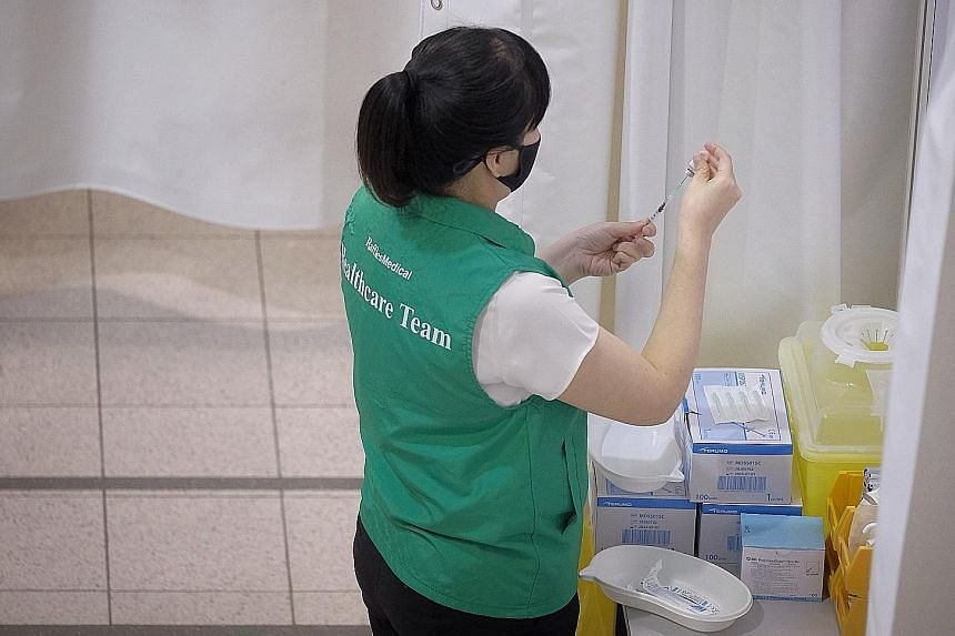 A nurse diluting the Covid-19 vaccine in a trial run yesterday. Seniors are prioritised in the vaccination campaign, with Tanjong Pagar and Ang Mo Kio as the pilot sites.