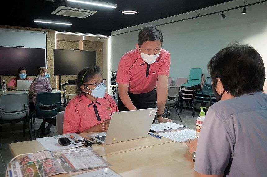 Trade and Industry Minister Chan Chun Sing speaking with a resident booking his time slot for the Covid-19 vaccination at the community vaccination centre in Tanjong Pagar Community Club yesterday. Volunteers also help the elderly in arranging for th
