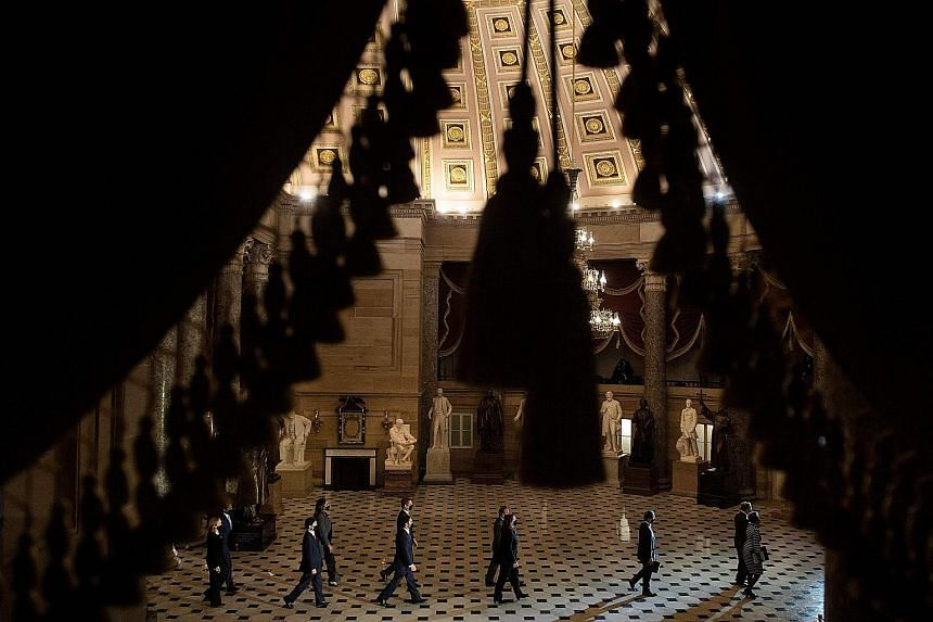 The group walking through the US Capitol's Statuary Hall. They followed the path that a mob took during the Jan 6 attack.