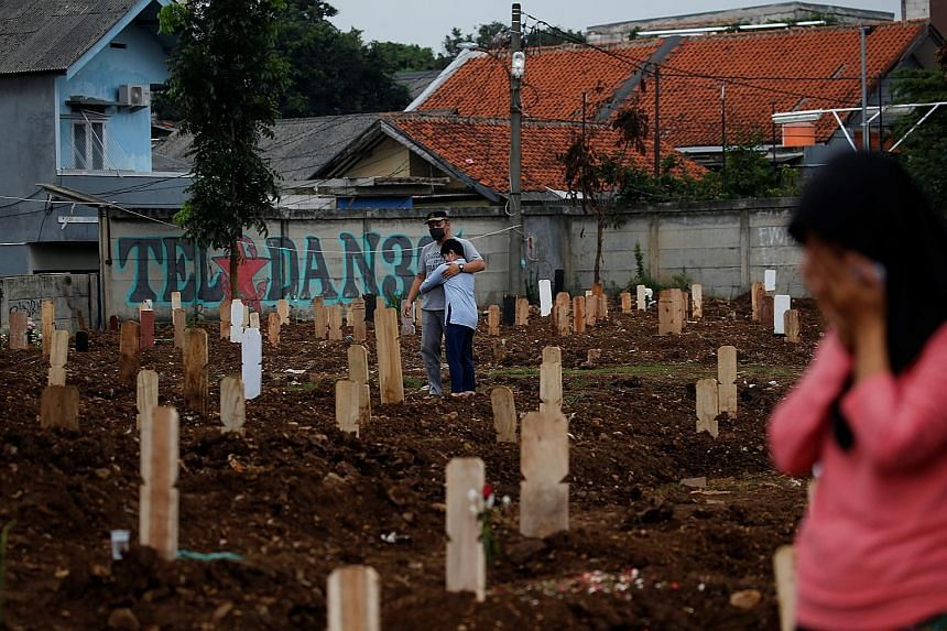 Mourners at Srengseng Sawah cemetery complex, a burial area in Jakarta provided by the government for Covid-19 victims, on Monday.