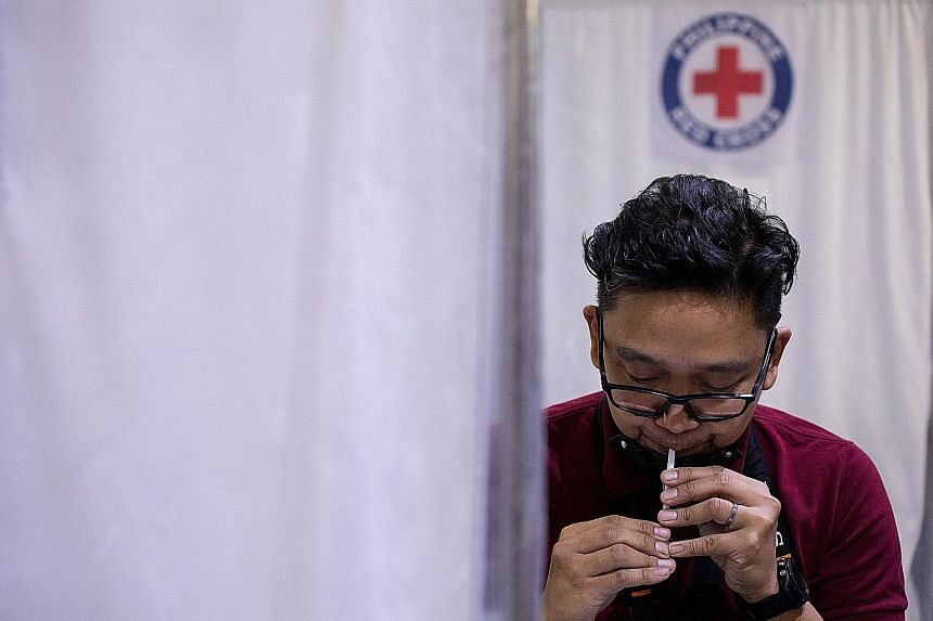 A man giving a saliva sample to test for Covid-19 at a laboratory in Mandaluyong City, Metro Manila, on Monday. The Philippines' caseload of more than half a million infections is one of the highest in South-east Asia.