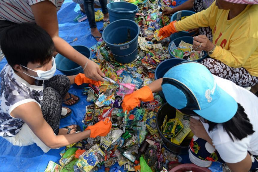 Volunteers sort plastic waste on the shore of Freedom Island, Philippines, during a cleanup organised by green groups.