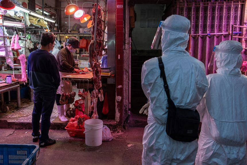 Civil servants in protective gear stationed at a building to check on residents in Hong Kong's Jordan neighbourhood on Monday, after officials locked down an area there on Saturday and ordered mandatory Covid-19 testing. The health authorities have s