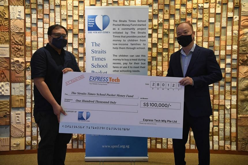 Express Tech Manufacturing managing director Leong Yoke Ming (right) handing over the cheque for $100,000 to ST School Pocket Money Fund board trustee Zakir Hussain on Jan 28, 2021.