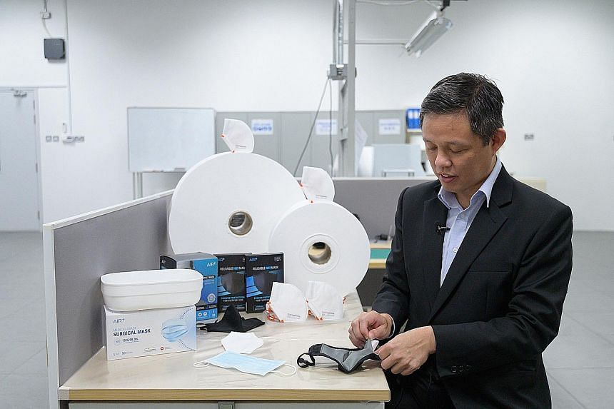 Trade and Industry Minister Chan Chun Sing inserting the filter produced by ST Engineering into a reusable mask yesterday, during a visit to the local firm. Singapore will build up its stockpile of these filters for future needs.