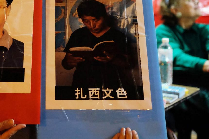 A volunteer holding a placard of Tashi Wangchuk in Beijing on June 4, 2017.