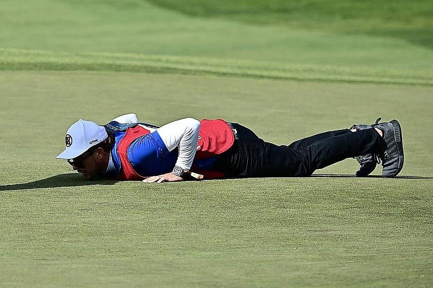 Patrick Reed's caddie on all fours at the fifth green to help line up his putt in the opening round of the Farmers Insurance Open in San Diego on Thursday. The American is tied with Swede Alex Noren for the lead at eight under.