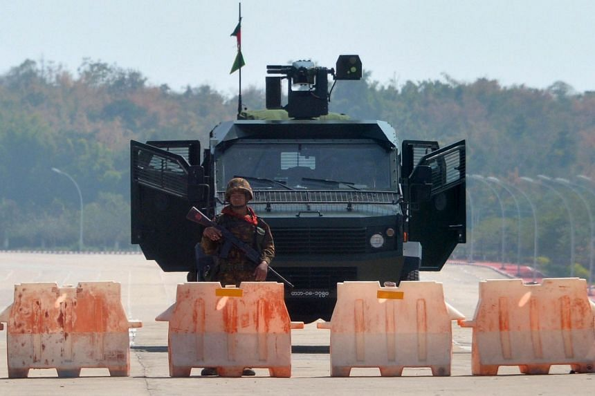 A soldier standing guard in front of an armoured vehicle on a blockaded road to Myanmar's Parliament in Naypyidaw on Feb 1, 2021.