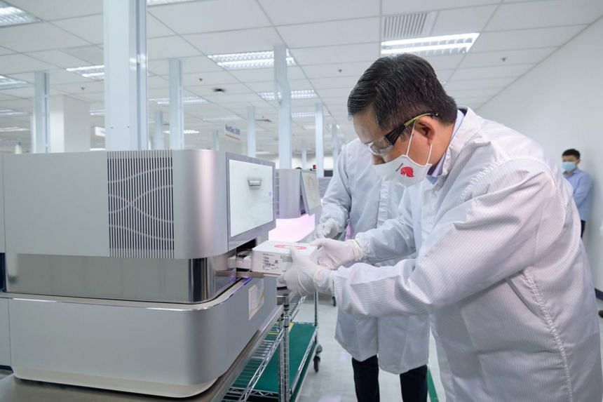 Trade and Industry Minister Chan Chun Sing looks at one of biotech firm Illumina's machines during a tour to the company's facility on Feb 1, 2021.