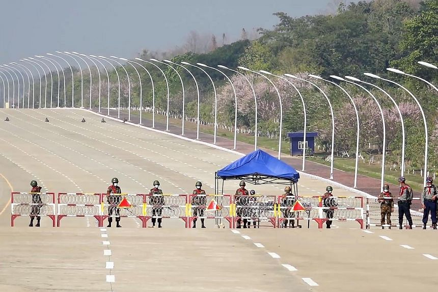 Soldiers standing guard on a road leading to Myanmar's Parliament building in Naypyitaw yesterday, after the military detained the country's civilian leader Aung San Suu Kyi and President Win Myint. Above: Myanmar soldiers seen inside Yangon City Hal