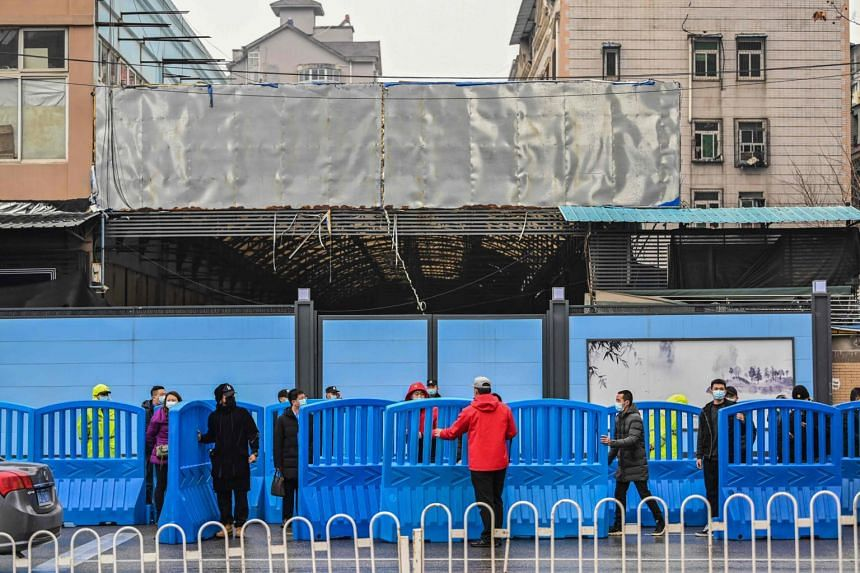 Workers place barriers outside the closed Huanan Seafood wholesale market during a visit by WHO members in Wuhan, on Jan 31, 2021.