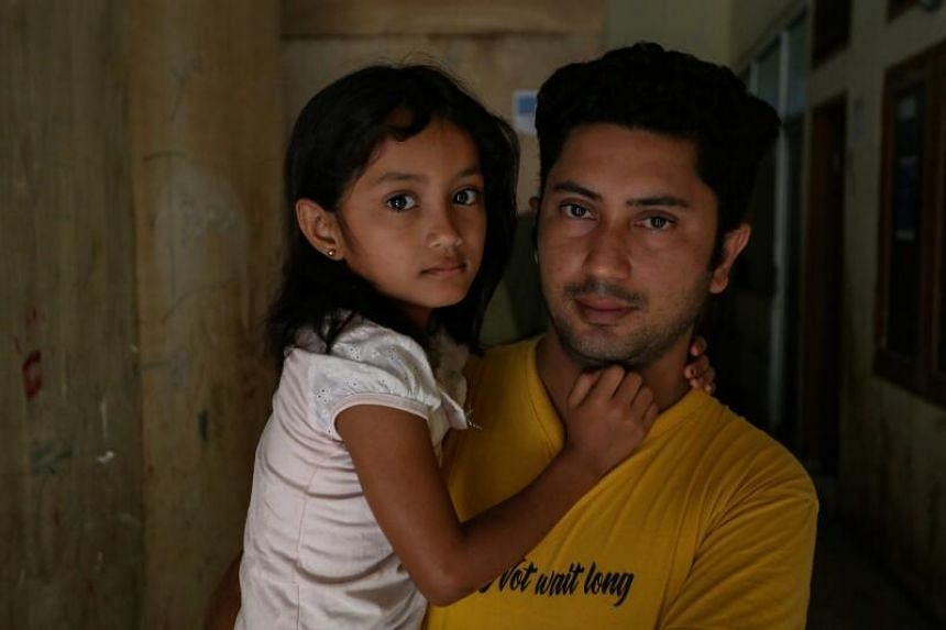 Mr Namashah holding his daughter at a makeshift camp in Lhokseumawe, Aceh province, on Jan 30, 2021.
