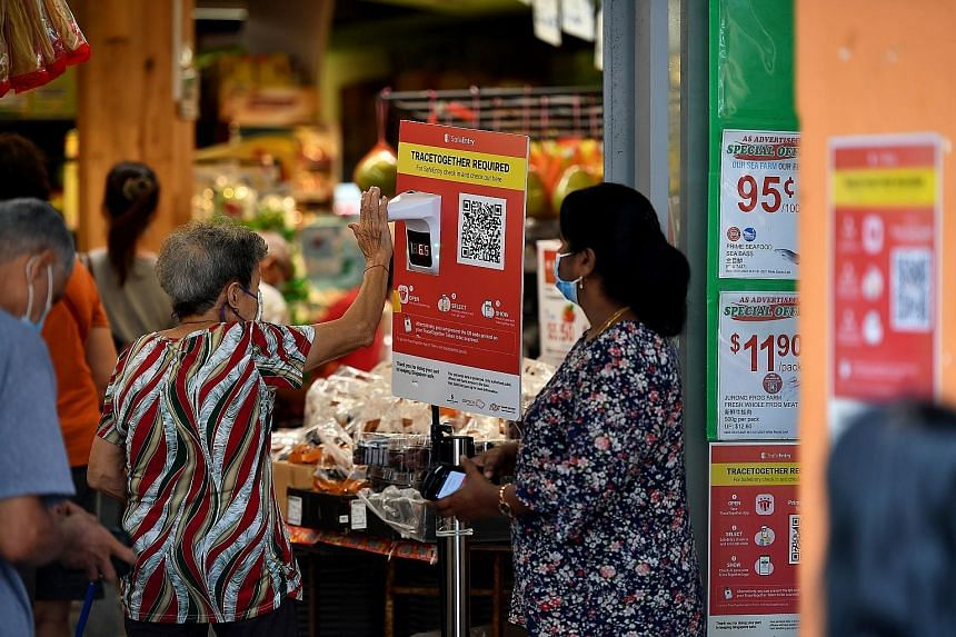 A temperature scanner and poster on TraceTogether at the entrance of Prime Supermarket in Tampines Street 81. Under changes to the law passed yesterday, contact tracing data from TraceTogether can be used for police investigations only for seven cate