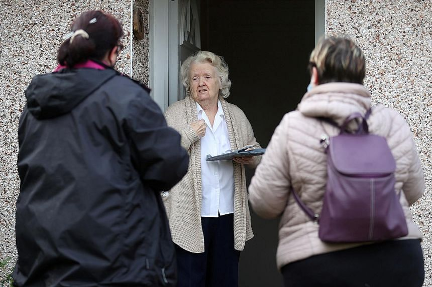 Volunteers handing out Covid-19 home test kits yesterday to residents in Goldsworth and St Johns in Woking, Britain, amid the coronavirus outbreak. To contain new outbreaks, residents in eight areas of the country will be tested, starting from yester