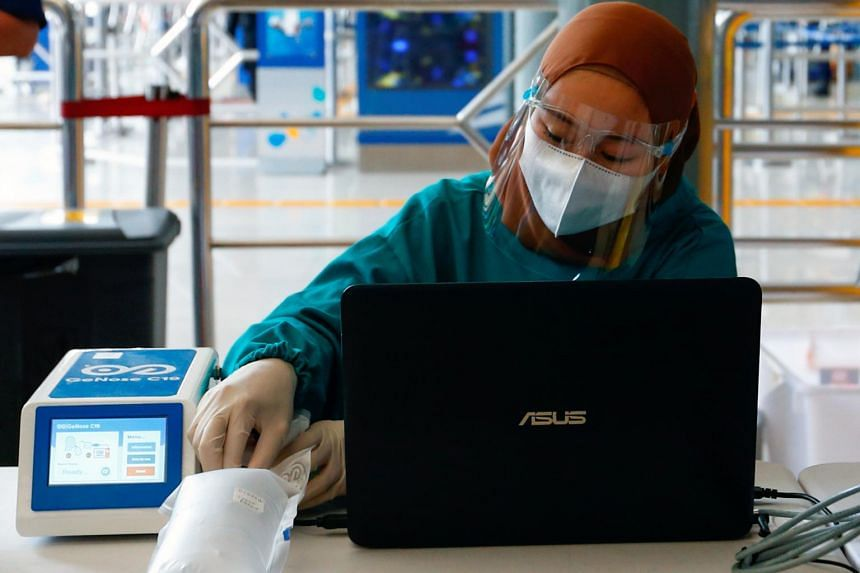 A healthcare worker tests an air-sample of a commuter using GeNose C19 in Jakarta on Feb 3, 2021.