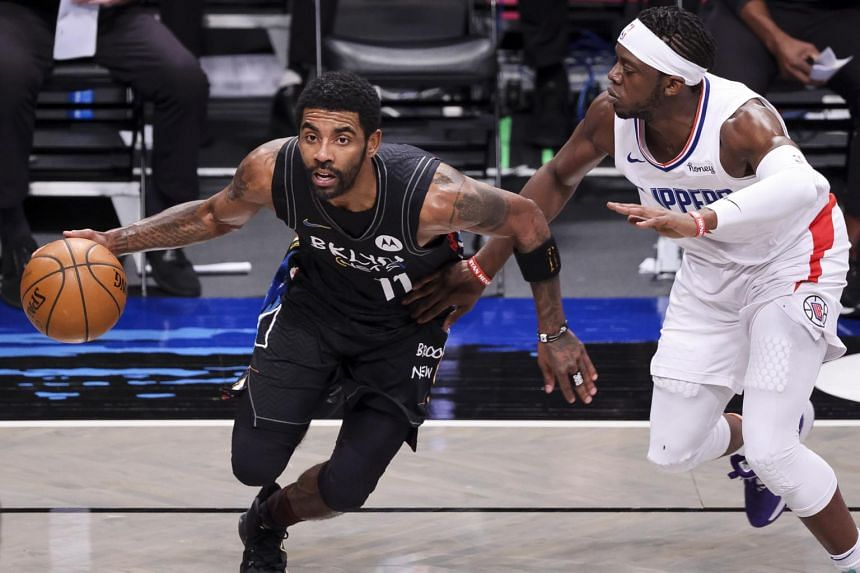 Kyrie Irving (left) drives past the Clippers' Reggie Jackson during the NBA basketball game at the Barclays Center in Brooklyn, New York, on Feb 2, 2021.
