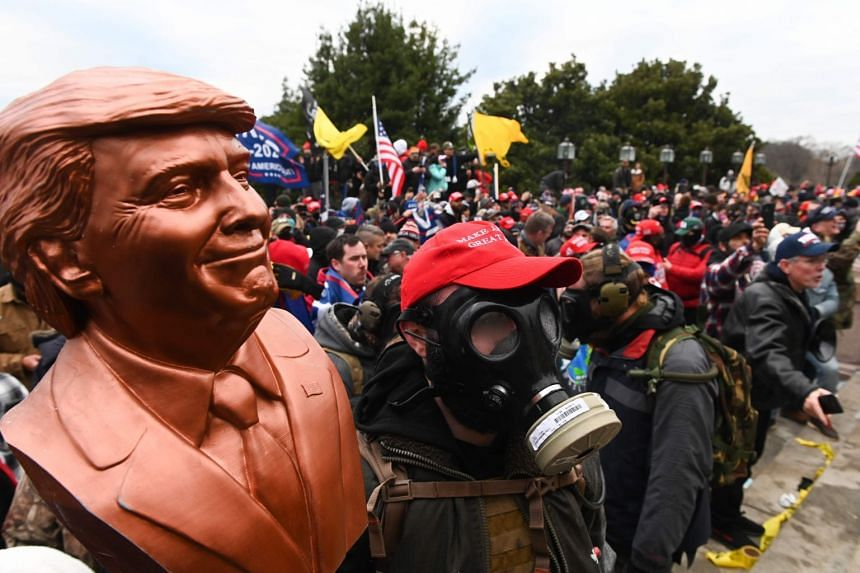 A Trump supporter wears a gas mask and carries a Trump bust after he and hundreds of others stormed stormed the Capitol building on Jan 6, 2021, in Washington, DC.
