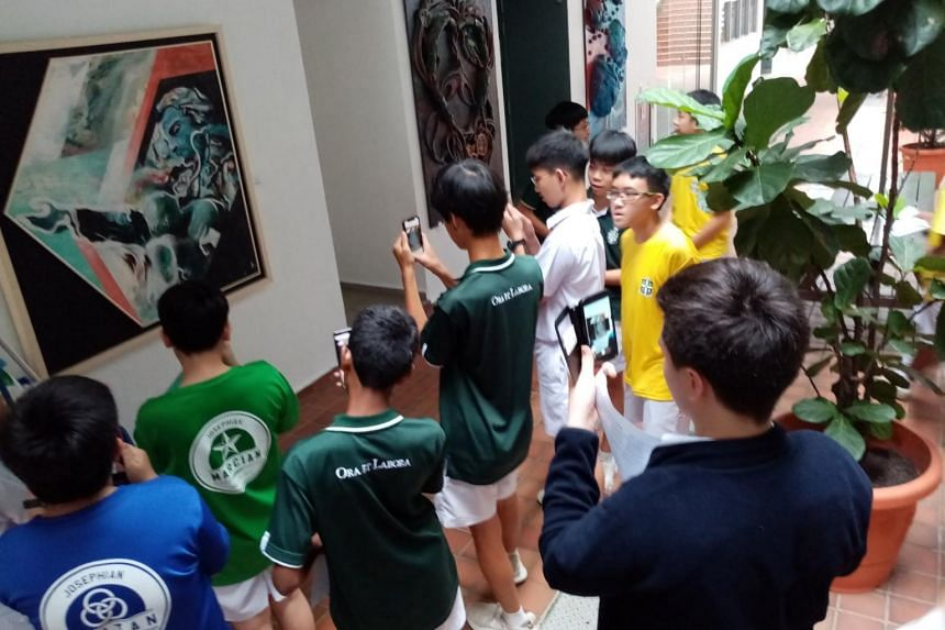 St. Joseph's Institution students testing an augmented reality prototype on a piece of artwork.