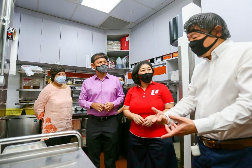 Senior Minister of State for Manpower Zaqy Mohamad (second from left) and U SME director Yeo Wanling (second from right) visit Jumbo Seafood restaurant in Upper Circular Road on Feb 4, 2021.