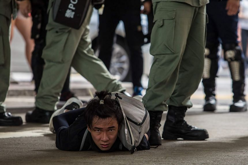 Riot police detain a man as they clear protesters taking part in a rally against a new national security law in Hong Kong on July 1, 2020.