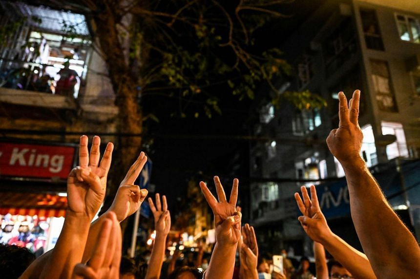 People give a three-finger salute after calls for protest went out on social media in Yangon on Feb 3, 2021.