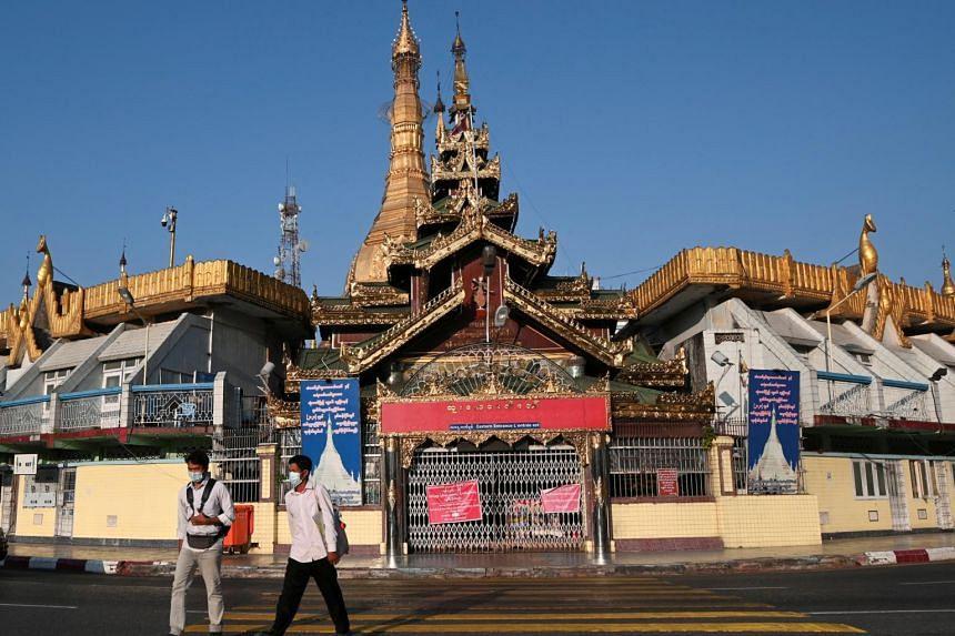 Men walk in front of the Sule pagoda in Yangon, on Feb 1, 2021.
