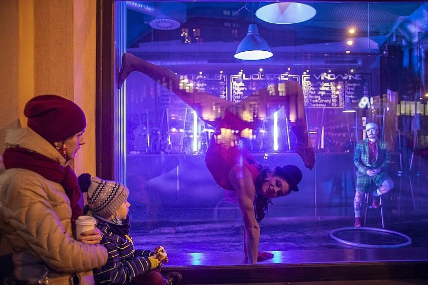 MOVING SHOWS: Artistes perform in closed shops and bars in Prague, in the Czech Republic, in an event organised by contemporary circus company Cirk La Putyka. Since the middle of October last year, all theatres in the country have been closed to stem