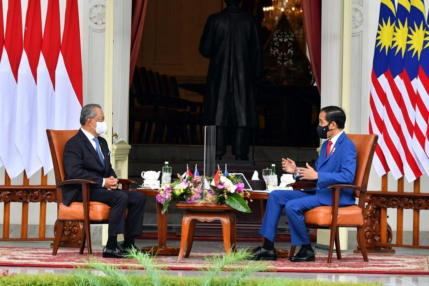 Indonesian President Joko Widodo with Malaysian Prime Minister Muhyiddin Yassin during a meeting at the Presidential Palace in Jakarta on Feb 5, 2021.