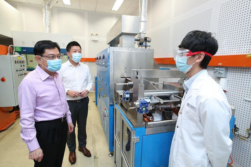 DPM Heng Swee Keat (left) being shown the fabrication process of lithium batteries by engineer Kevin Tan, during a visit to the Durapower R&D labs on Feb 5, 2021.