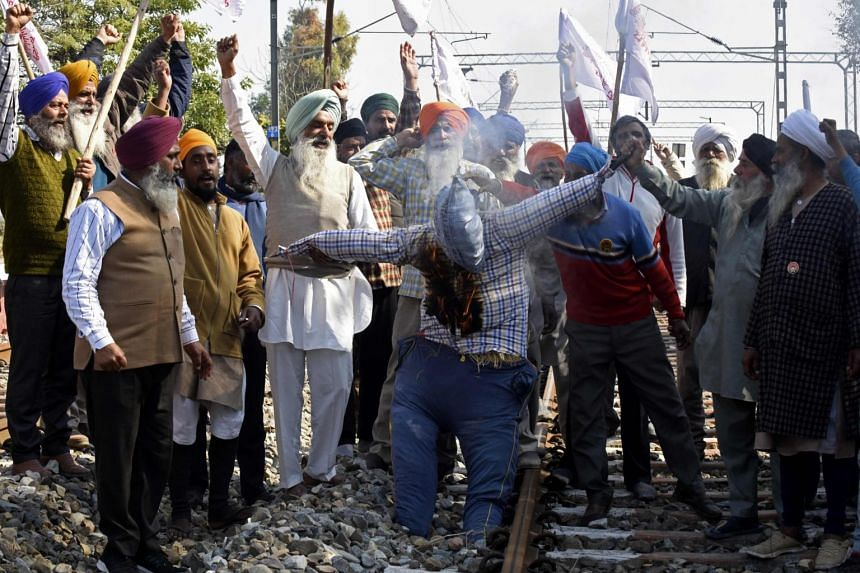 Farmers burn an effigy of Indian Prime Minister Narendra Modi during a protest on the outskirts of Amritsar on Feb 5, 2021.