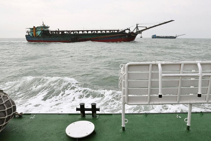 Sand-dredging ships with Chinese flags are seen from a Taiwanese coast guard ship patrolling in the waters off the Taiwan-controlled Matsu islands.