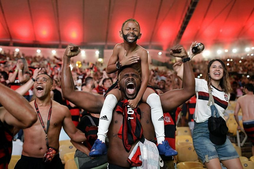 Fans of Brazil's Flamengo football team cheering as Gabriel Barbosa scored a goal against defending champions River Plate of Argentina, in the final of the Copa Libertadores, broadcast on giant screens during a watch party at Maracana Stadium in Ri
