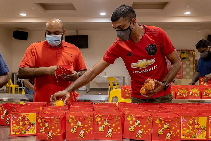 Goodie bags for the festive season being packed at Sri Mariamman Temple in South Bridge Road yesterday. Volunteers at the temple also prepared Chinese New Year lunch for about 370 elderly people.