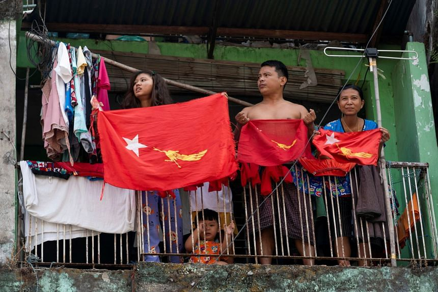 People holding National League for Democracy party flags on their balcony during a protest against the military coup, in Yangon, Myanmar, on Feb 7, 2021.